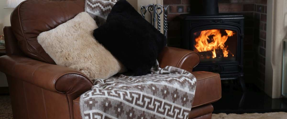 Alpaca throws on a leather chair by a real fire